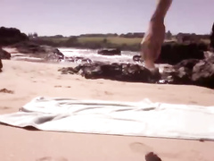 Young guy is lying on the beach and wanking dick