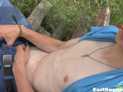 Cute twink is sucking candy and jerking off on the bench