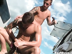 Sexy young boyfriends are taking shower outdoor from camping trailer
