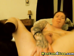 Tattooed hunk in black socks enjoys masturbating dick